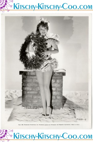 Iris Adrian posing atop a roof in a festive holiday romper and holding a wreath